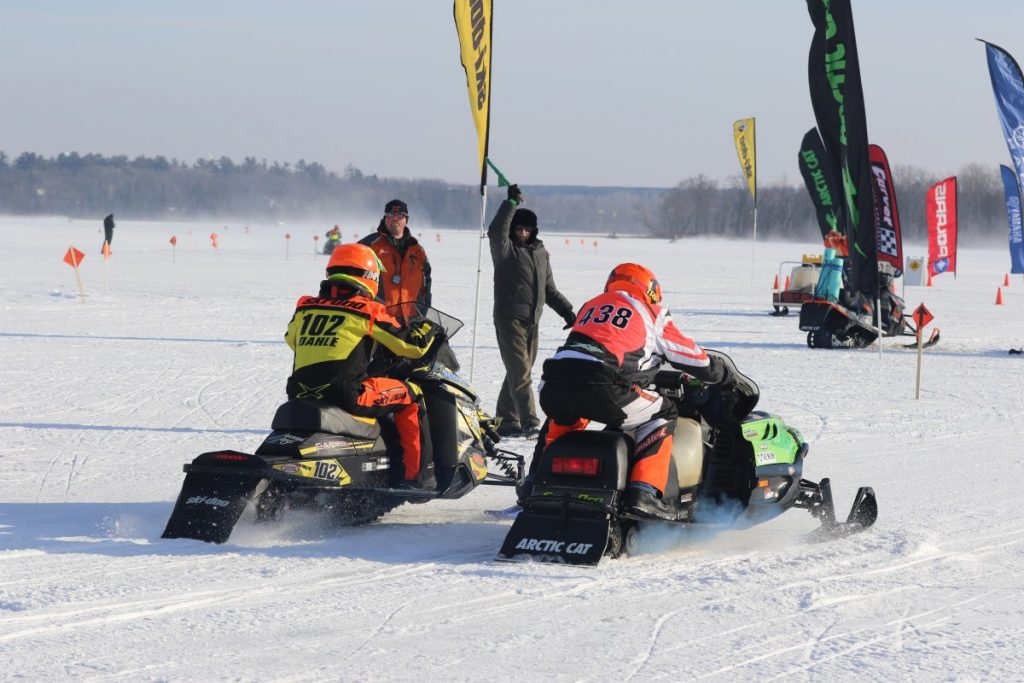 Snowmobile Hall of Famer Jack Hausner starts off the 47th Annual Naytahwaush Nightriders Sno-Deo with a wave of the flag and the racers were off in the first card of races. Photo provided by Tom McArthur.